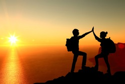 The Silhouette of two man with success gesture standing on the top of mountain