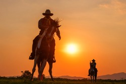 The silhouette of two men wearing a cowboy outfit with a horse and a gun held in the hand