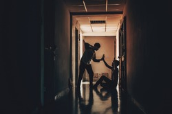 The silhouette of two young men conflict fighting with each other in  the old condo