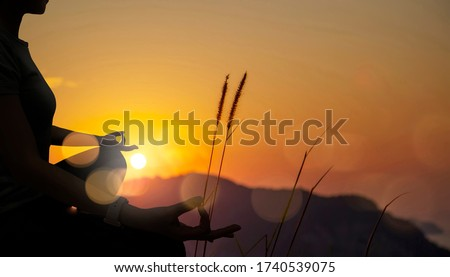 The silhouette of woman sitting yoga alone,Relax and meditate,mental health concept with nature spiritual. Stok fotoğraf ©