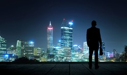 The silhouette portrait of businessman on the roof to see the city skyline scenery.