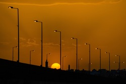 The silhouetted street lights along the road against the golden sunset sky, Riyadh, Saudi Arabia