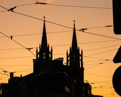 the silhouettes of a church with gothic architecture and electrical cables at sunset