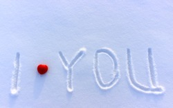 The simple innocent inscription written by hand I love you on a white clean snow with with place for writing. A declaration of love as a background on Valentine's Day. Red heart on snow