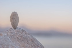 the simple stone stands vertically in balance, calm, peaceful meditational background in pastel colors