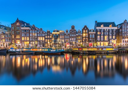The Singel is a canal in Amsterdam which encircled the city in the Middle Ages. This famous part of the canal has spectacular houses and houseboats. Stockfoto ©