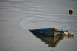 The sinking wooden boat in the lake