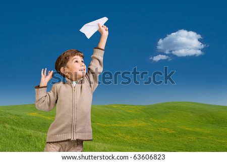 The six-year boy starts the paper plane against a landscape