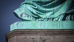 The size 879 foot of the Statue of Liberty rising off its pedestal.