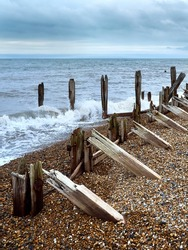 The skeletal ruins of a breakwater with waves crashing over it on a shingle beach under a clouded sky.