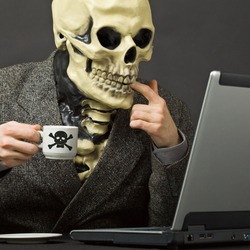 The skeleton drinks poisonous coffee sitting at a table with the laptop