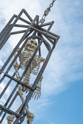 The skeleton of a man in a metal old cage. Torture chamber, pirate.