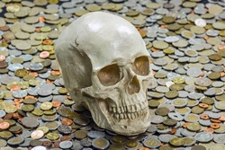 The skull is among a heap of different coins