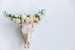the skull of an animal on the wall is decorated with flowers. Bull skull with horns