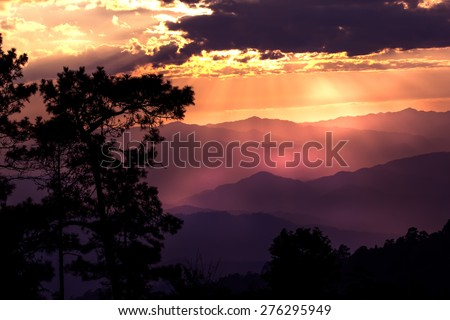 The Sky and sun beam at sunset,Cloud with dark shadow,Black tree in shadow.Mountain at background.Sun nearly go down.