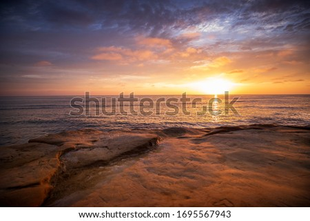 The sky erupts in vibrant colors, as the sun sets over the Pacific Ocean, at Sunset Cliffs in San Diego, California.