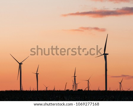 The sky glows behind a silhouetted wind farm at sunset #1069277168