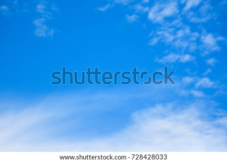 The sky is blue and the clouds are blurry.