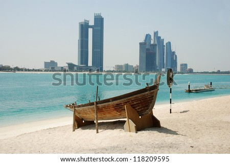 The skyline of abu dhabi with a boat in front