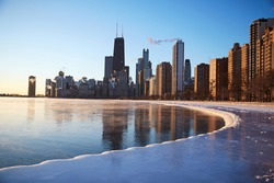 The skyline of Chicago during sunrise one frigid winter morning with the lakefront turned to ice
