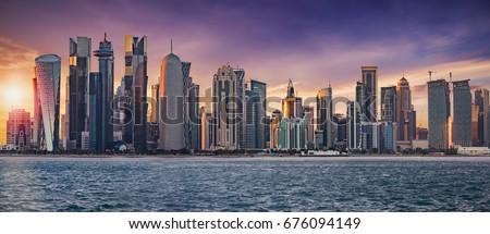 The skyline of Doha, Qatar, on a cloudy sunset #676094149