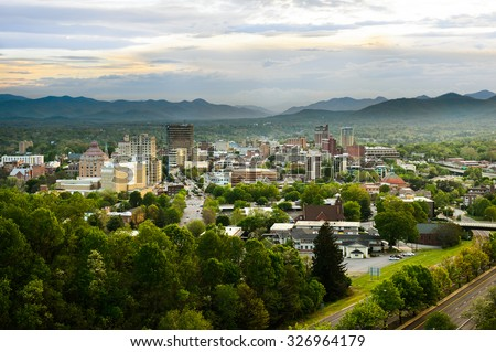 The skyline of downtown Asheville, North Carolina at sunset with mountains in the background
