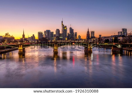 The skyline of Frankfurt at sunset, seen from a bridge at the river Main at a cold day in winter.
