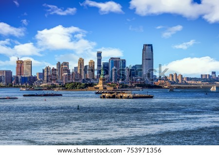 The skyline of Jersey City, New Jersey from New York Harbor with the Statue of Liberty in the foreground