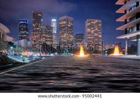The skyline of Los Angeles after dark, with fountains.