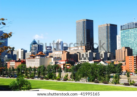 The skyline of Montreal with old harbor park and china town in foreground.