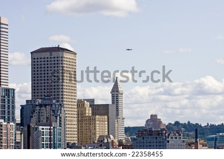 The skyline of Seattle on a sunny day with a helicopter flying over