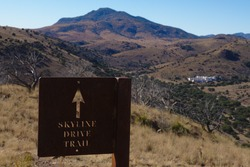The Skyline Trail sign at the terminus in Fort Davis Mountains State Park in Fort Davis, Texas. The Indian Lodge can be seen in the distance.