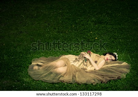The sleeping beauty lays on the grass