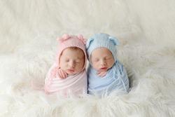 The sleeping Newborn girl and boy lies on the white fur. Newborn twins
