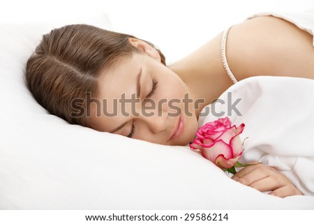 The sleeping young woman holds a rose in a hand, isolated