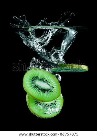 The slices of kiwi falling into water .