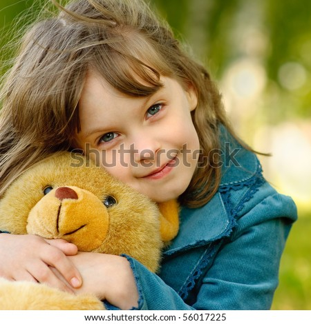 The small beautiful girl embraces an amusing bear cub against the summer nature.