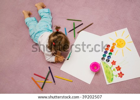 The small beautiful girl paints on a paper lying on a floor