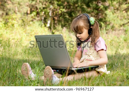 The small beautiful girl works on a computer, sits on a  green lawn - stock photo