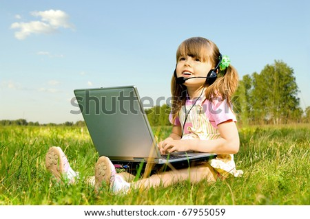 The small beauty girl works on a computer, sit on green lawn, Smile
