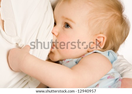 The small blue-eyed girl sucks a breast close up - stock photo