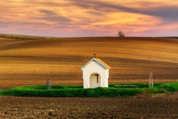 The small chapel surrounded by wheat fields during sunset. Beautiful colorful spring landscape in South Moravia, Czech Republic.