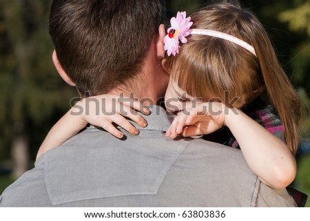 The small crying girl on a shoulder of the father