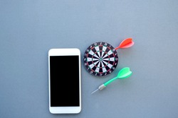 The small dartboard and the arrow located with telephone represent successful business goals concept.