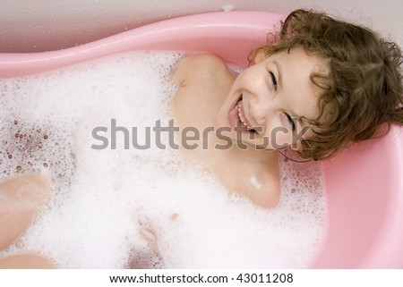 The Small girl bathes in bath.