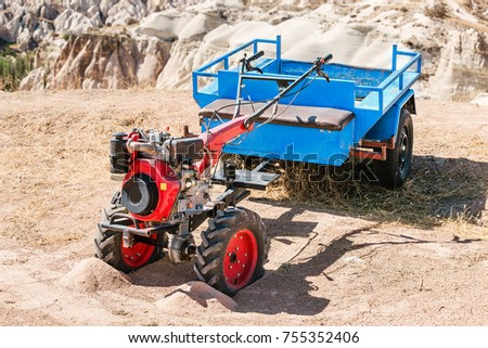 The small handy farm machine motor plow with cart closeup standing in deserted rural landscape in sand