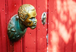 The small metallic head of human, as handle on the red door.