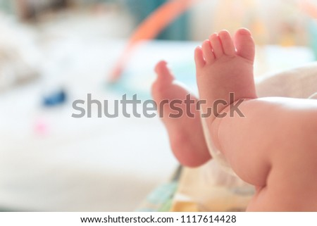 The small tiny cute feet of the infant. Blurred light background.
