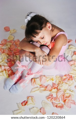 The small tired ballerina sits on a floor in rose-petals