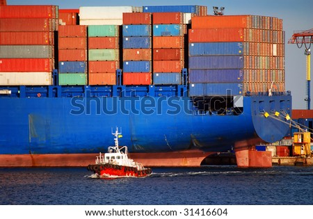 The small tugboat accentuates the size of the large container ship stern part with cargo containers